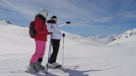 admires : Skiers Saw Interesting In The Mountain Valley And Show Each Other