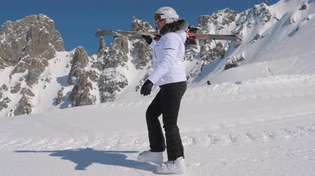 goes : In Mountain Ski Resort A Skier Go Forward With Downhill Ski On Her Shoulder