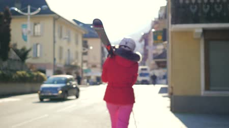 goes : Woman Walking Near Houses Holding Her Alpine Ski On The Shoulder Before Skiing