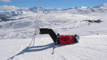 hegyoldalban : Skier Resting In The Mountains Lying On The Snow And Legs Up With Skis
