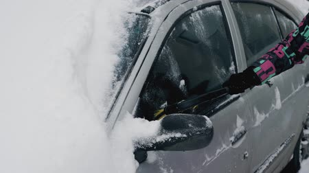 vassoura : A Woman Cleans Her Car From Snow In The Winter With A Brush