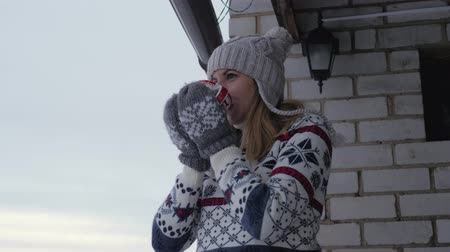 veranda : Woman Stands On The Veranda In The Winter In Sweater And Drinks A Cup Of Coffee Dostupné videozáznamy
