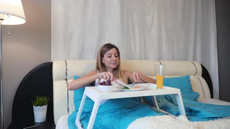 huevos revueltos : Motion The Camera To A Woman In Bed Who Eats A Delicious Breakfast On A Stand