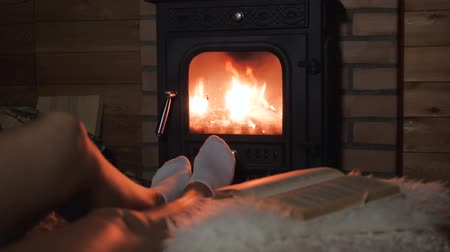 log cabin : Women Feet Lie Comfortably And Warm By The Warm Fire Of The Fireplace