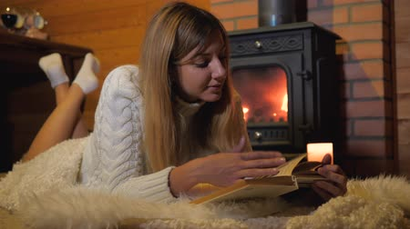 yumuşaklık : Woman Lying On A Soft Carpet By The Burning Fireplace And Reading A Book Stok Video