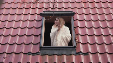 breathing fresh air : Shot From The Street The Woman Wrapped In A Blanket Opens The Roof Window Stock Footage