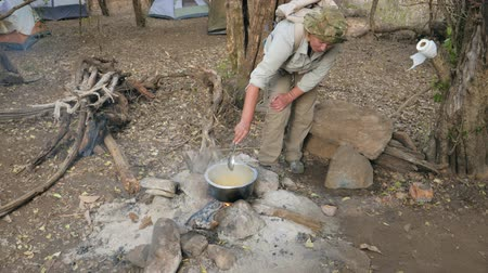 konvice : Tourist At Camping Stirred With A Spoon To Cook Pasta In A Saucepan On The Fire Dostupné videozáznamy