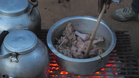 coals : Hand Raises The Lid Of The Pan And Stir The Chicken With A Spoon
