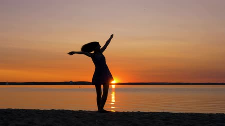övgü : Woman Runs Towards Sunset On The Beach Raising Her Hands Up And Turning Around Stok Video