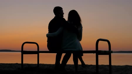 comes : Loving Couple Sitting On A Bench In An Embrace On The Beach And Enjoy The Sunset Stock Footage