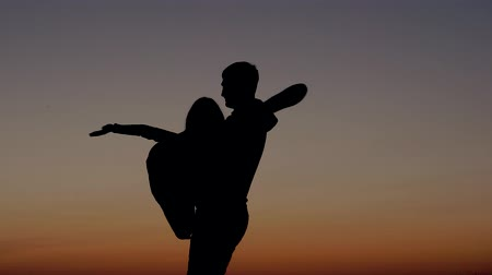 romance : Silhouette Of A Man Holds On Hands Woman And Circling Her At Sunset Sky