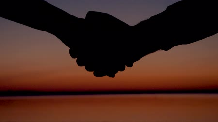 solidarita : Close-Up Of Handshake At Scarlet Sunset