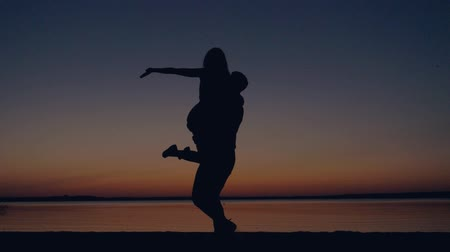 алый : Silhouette Of Romantic Couple Kissing At Sunset A Man Holding Woman And Spinning Стоковые видеозаписи