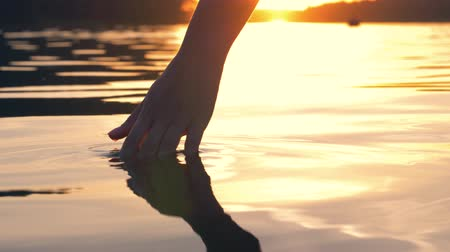 elevação : Hand Gently Touches The Surface Of The Water In The Golden Sunset Stock Footage