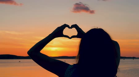 escarlate : Woman At Sunset Makes A Hand Heart