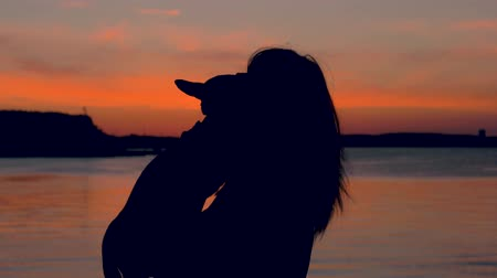 escarlate : Silhouette Of A Woman At Sunset Holding Her Dog Lovingly Kisses Her