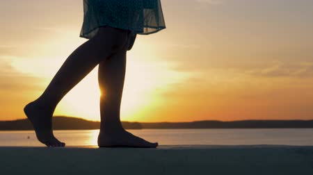 večer : Close-Up Of Women Feet Are On The Beach In The Flicker Rays Of The Sunset