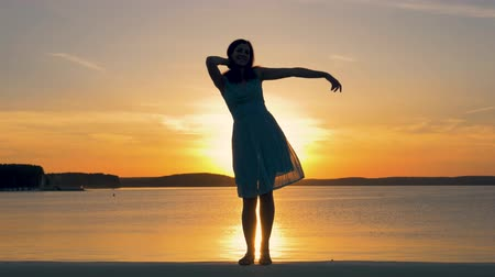 raises : Silhouette Of Pretty Woman Dancing And Posing At Camera On Background Of Sunset Stock Footage