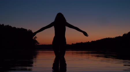 braços levantados : Woman Stands Knee-Deep In The Water Of The Lake At Sunset Raises Her Arms Up