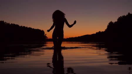 elevação : Silhouette Of A Woman Running Knee Deep In The Water Of The Lake At Sunset
