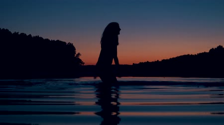 escarlate : Silhouette Of Woman Stands Knee Deep In The Lake At Sunset And Splashes Water