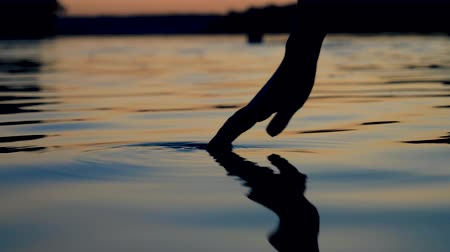 gondos : Gently Touches The Surface Of The Water With Your Fingertips In The Sunset Stock mozgókép