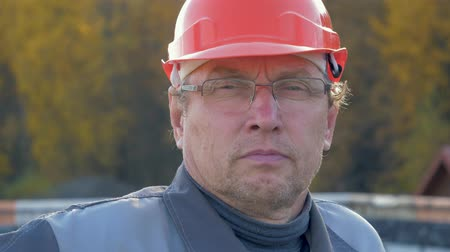 hard hat : Close Up Portrait Of Caucasian Builder In Helmet And Glasses Looking At Camera