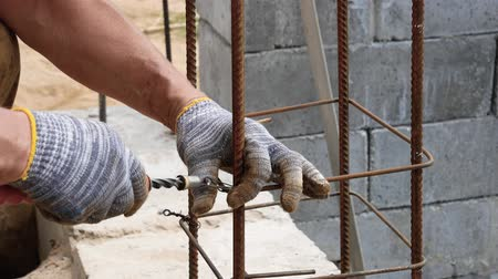 knotted : Hands Builder In Dirty Gloves Tied Steel Wire On Rebar Tool On Construction Site Stock Footage