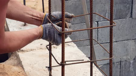 фиксация : Hands Builder In Dirty Gloves Tied Steel Wire On Rebar Tool On Construction Site Стоковые видеозаписи