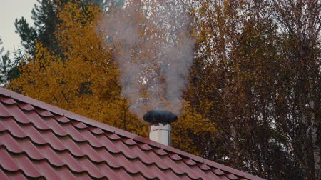 кафельный : White Smoke From Chimney Of A House On A Red Tiled Roof On A Cold Autumn Evening Стоковые видеозаписи