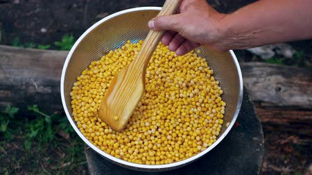 горошек : Cooks Hands Stir Chickpeas With A Wooden Shovel In A Colander