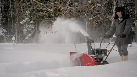 arado : Man Cleans Snow With A Snow Plow On The Background Of The Forest In Winter