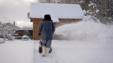 snow removal : Man Cleans Snow With Snow Plow Background Of Wooden House In Winter