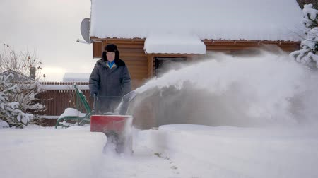 snow plow : Man Cleans Snow With Snow Plow Background Of Wooden House In Winter