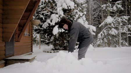 pikk : Man Cleans The Yard With A Shovel From The Piles Of Snow In The Winter