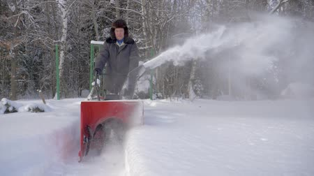 arado : Man Cleans Snow With Snow Removal Machine Background The Forest In Winter