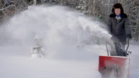 snow plow : Man Cleans Snow With Snow Removal Machine Background The Forest In Winter