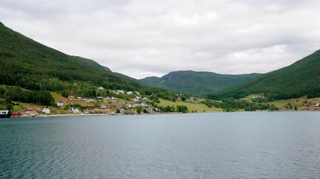 строгий : Sail On The Beautiful Bay Of Norwegian Fjords Against The Hills With The Village