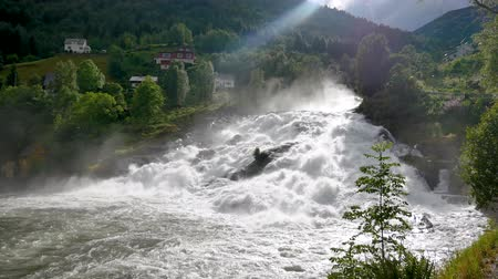 スカンジナビアの : Waterfall Flows From Hills With Green Grass And Ray Of Sun Illuminates Rapids