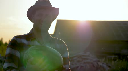 Caucasian Man Farmer In A Hat Holds In His Hands A Ripe Watermelon At Sunset