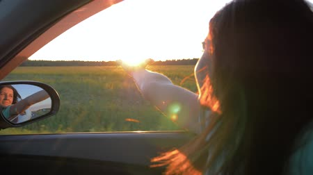 Happy Young Woman In Car And Hand Playing In The Air At Sunset Rays