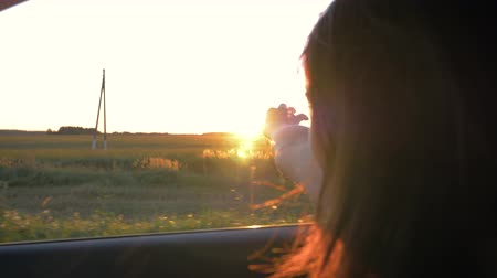 Pretty Young Caucasian Woman In Car And Hand Playing In The Air At Sunset Rays Wideo
