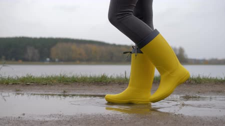 Legs Of A Woman In Yellow Boots Go Through Puddles On A Cloudy Autumn Day