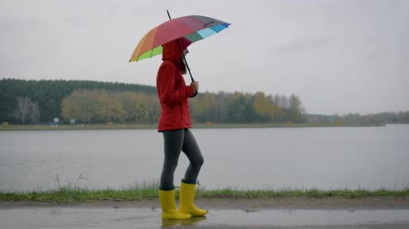 Woman In Yellow Boots And An Umbrella Goes Through The Puddles In The Autumn Day