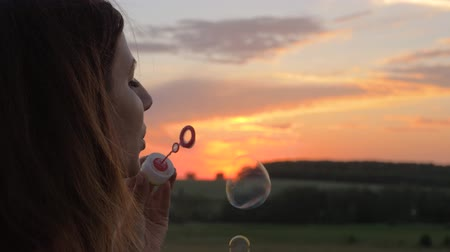 Happy Young Woman Blow Bubbles At Sunset On The Street