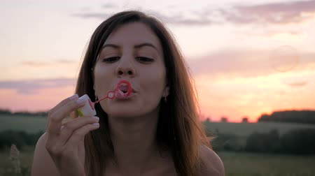 escarlate : Portrait Of Smiling Young Pretty Woman Blowing Bubbles In The Evening At Sunset