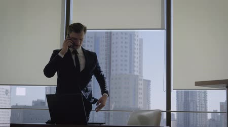meeting negotiate : Businessman Talking On Phone At Office Window Then Sits Down To Workplace Stock Footage
