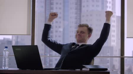 Successful Businessman In The Office Raises His Hands Up In A Sign Of Victory
