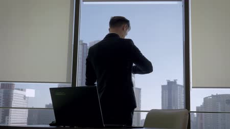Director In Office At The Workplace Standing At Window And Looks At His Watch