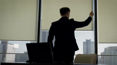 biznesmen : Businessman In Office Standing At Window And Opens The Blinds To Make Brighter